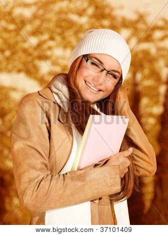Image of cute businesswoman holding folder with documents, beautiful student girl wearing warm hat and scarf with elegant glasses, smart young lady enjoying autumnal educational period