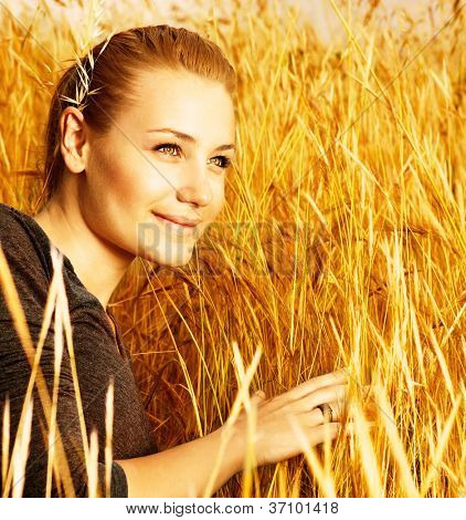 Photo of attractive smiling girl sitting in golden wheat field, closeup portrait of beautiful young blond female on yellow hay ryes background, grain harvest season, conceptual of autumn season
