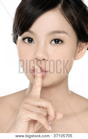 Young woman making a keep quiet gesture putting her finger on mouth