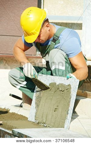 mason worker tiler making stairway from granite stone tile blocks
