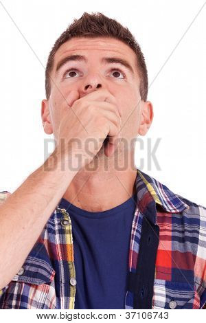 portrait of a surprised young man covering his mouth with hand and looking up over white