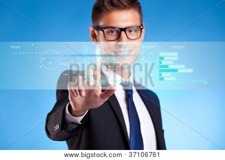business man  pushing some business graphs on a touch screen interface