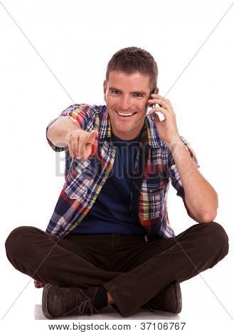 young man sitting on the floor, legs folded, talking on the phone, pointing and looking at the camera, while smiling. isolated on white