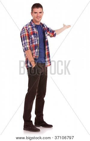Young man dressed casual is presenting something while holding his other hand in his pocket.