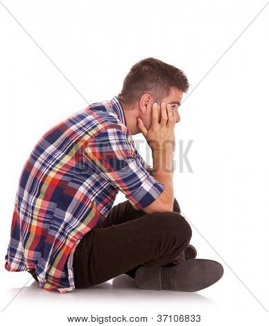 side view of a young casual man sitting disappointed with his face in his hands. isolated on white
