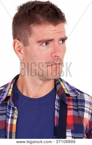picture of a young casual man looking suspiciously to a side of the camera. on white