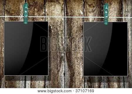 Photo frames with pins on rope over old aged wood background