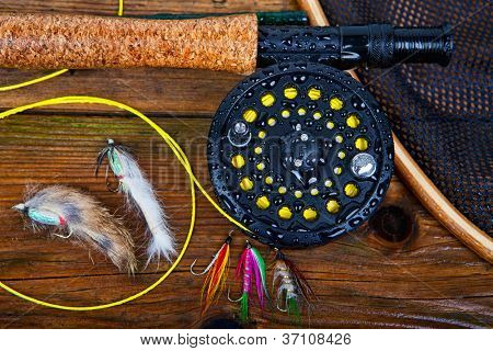 A fly fishing rod and reel on a wet wooden background, focus on the reel.