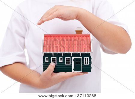 Protecting my home - child hands shielding small house, insurance and safety concept