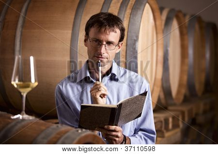 Winemaker in cellar analyzing a glass of white wine and taking notes in notebook.