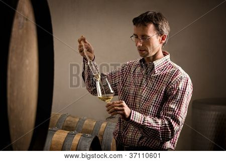 Winemaker in cellar taking sample of white wine from barrel for testing.