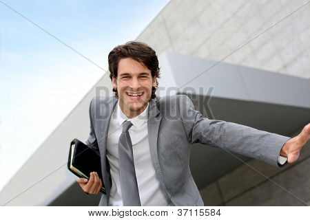 Happy successful businessman jumping in the air