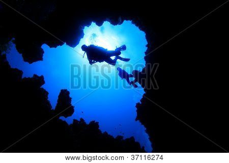 Scuba Divers descend into a deep underwater cave