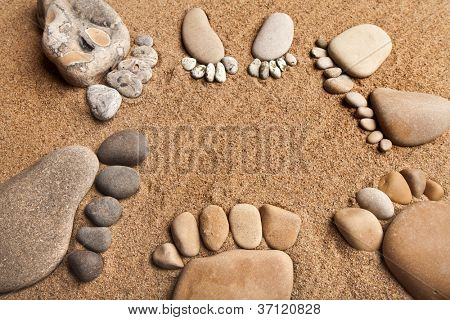 trace feet of a pebble stone on the sea sand backdrop , concept happy family
