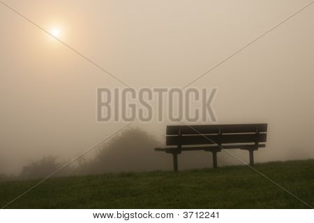 Misty Bench On A Hill Under The Raising Sun In The Morning Fog