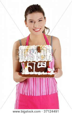Young housewife woman in apron holding gingerbread house model, isolated on white background