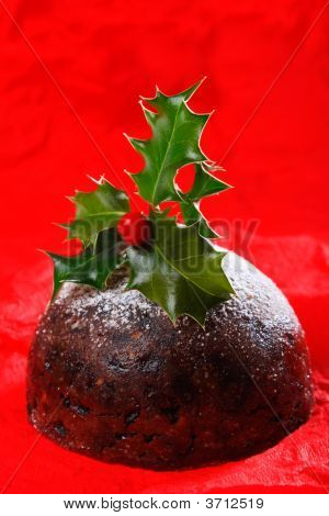 Chrismas Pudding With Holly Twig On Red Paper Background
