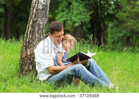 young father with his daughter read the Bible in the nature