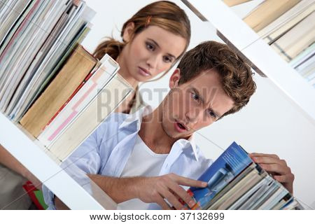 Man looking at a selection of books in shock