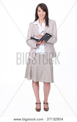 Young woman in a skirt suit writing in a personal organizer