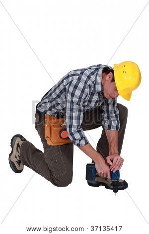 Man drilling hole in floor