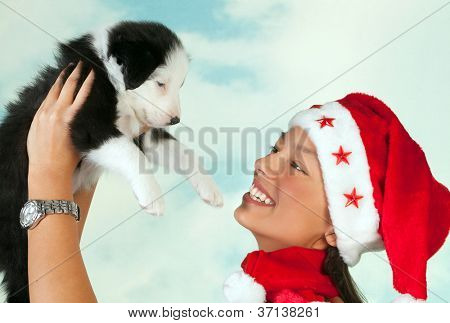 Beautiful girl with santa hat holding a cute little border collie puppy