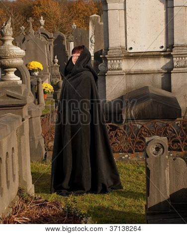 Widow with victorian cape visiting a very old graveyard