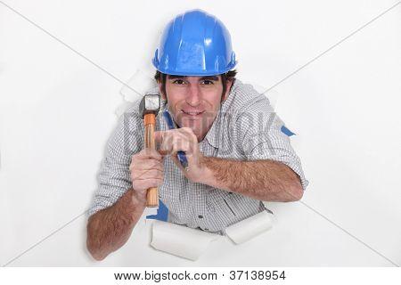 Man with hammer and nail tearing through