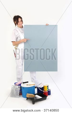 Female decorator pointing to a blank poster