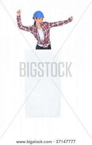 Enthusiastic construction worker with a board left blank for your message
