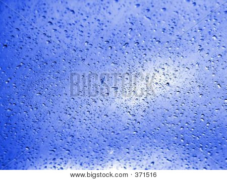 Raindrops On Windshield With Blue Sky Background