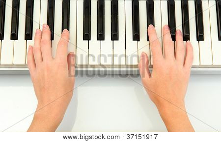 hands of woman playing piano