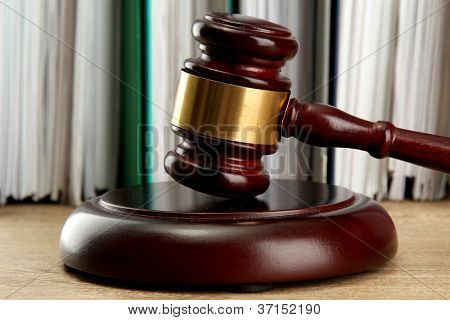 wooden gavel and folders on wooden table, close up