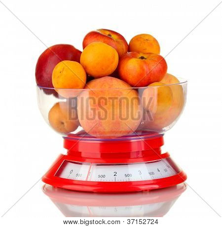 Ripe fruit in kitchen scales isolated on white