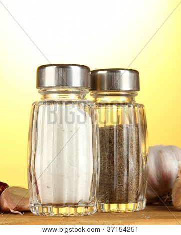 Salt and pepper mills and garlic  on wooden table on yellow background