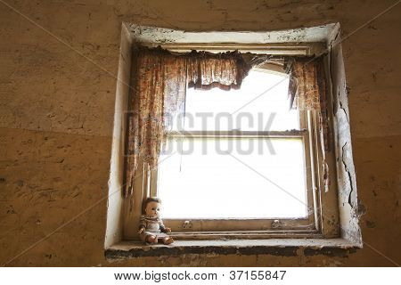 Old Vintage Doll Sitting On Sill Of Decrepit Window With Shredded Curtains