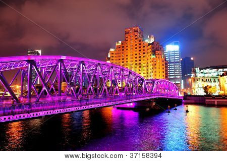 Shanghai Waibaidu bridge at night with colorful light over river