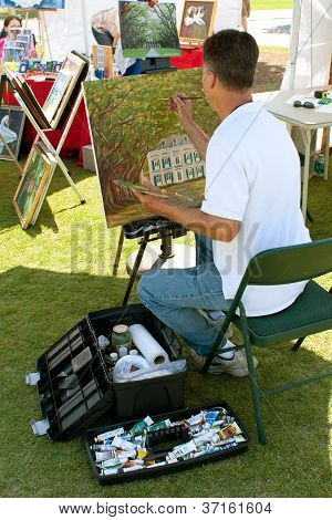 Artist Paints On Canvas At Outdoor Festival