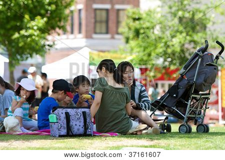 People Enjoy A Picnic Lunch At An Outdoor Festival