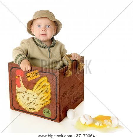 An adorable baby boy sitting in a wooden egg box.  He's concerned because of the broken eggs beside him.  On a white background.