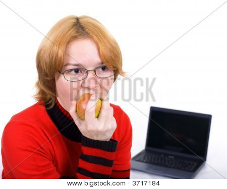The Woman Bites An Apple Against The Laptop