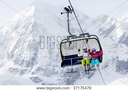 Skiing, winter - happy skiers on ski lift