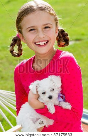 Happy childhood  - lovely girl with cute puppy in the garden