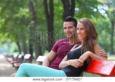 Handsome man embracing his girlfriend on a bench