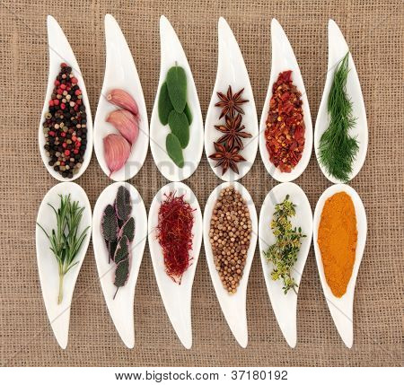 Herb and spice selection in white porcelain dishes over hessian background.