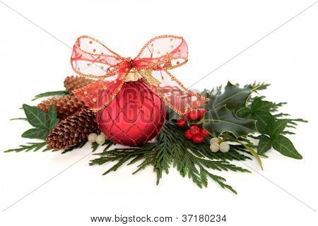 Christmas red sparkling bauble with glitter bow surrounded by holly, ivy, mistletoe and cedar leaf sprigs with pine cones over white background.