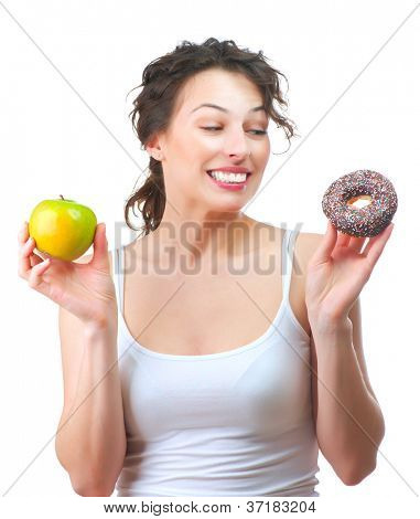 Diet. Dieting concept. Healthy Food. Beautiful Young Woman choosing between Healthy and Unhealthy Food.Fruits or Sweets. Isolated on a White Background