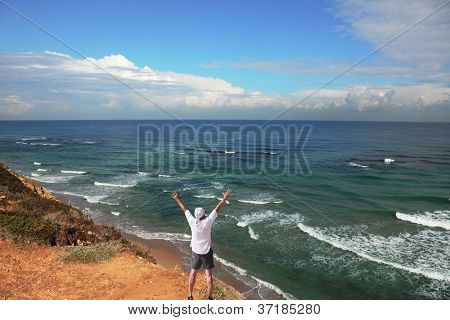 The enthusiastic tourist welcomes sunrise. Warm winter in Israel. Coast of Mediterranean sea
