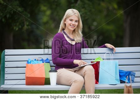 Portrait of happy young woman with shopping bags and tablet PC on park bench
