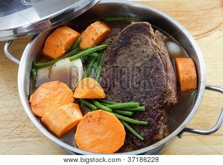 A traditional American pot-roast with beef, gravy, onion, sweet potato and green beans. This is at the cooking stage where the vegetables have just been added